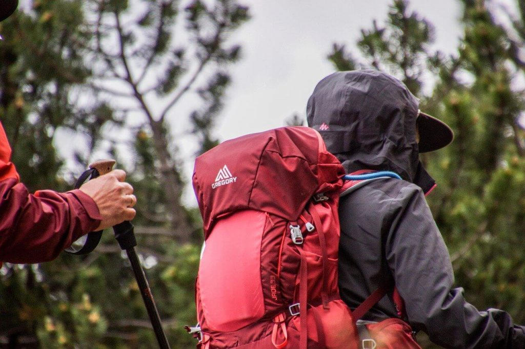 Hiker walking with red hiking backpack on