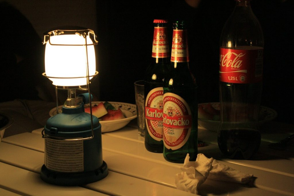 Camping light lantern next to beer bottles
