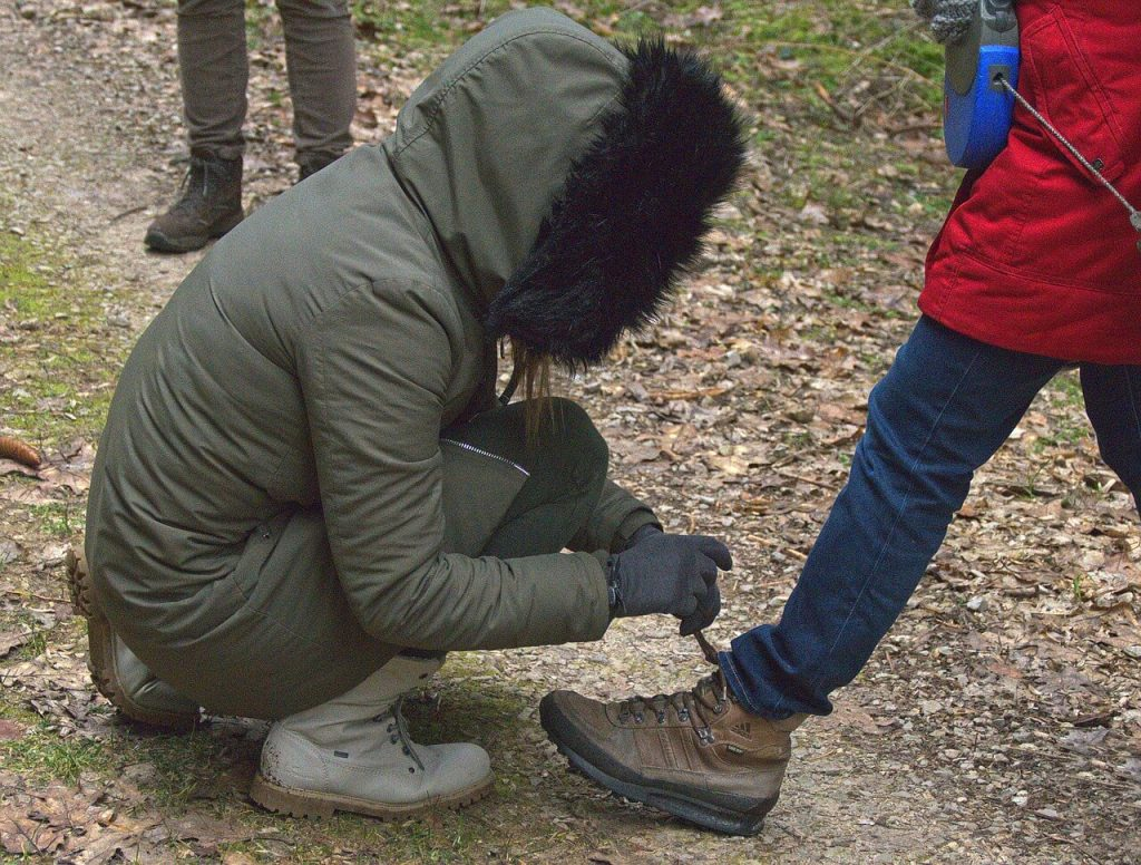 Woman tying someone's hiking shoes