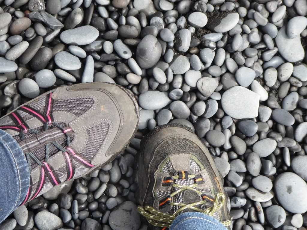 Two people wearing hiking shoes on rocks